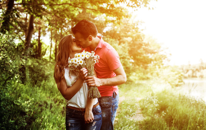 A couple in a forest field holding flowers and kissing in love